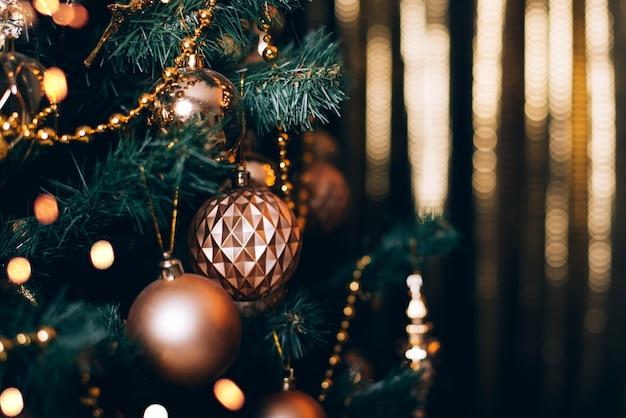 Ramo di abete con palline dorate e luci festive sullo sfondo scuro con scintillii.