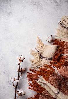 Ramo di cotone e coperta su sfondo chiaro
