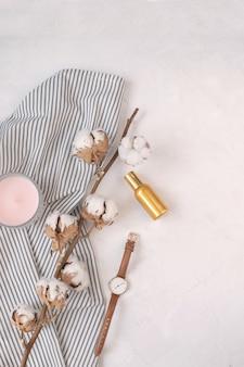 Ramo di cotone essiccato, candela, bottiglia di profumo, orologio su tovagliolo a righe spiegazzato