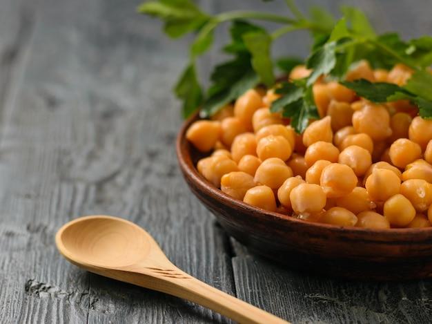 Ramo di prezzemolo su una ciotola con ceci bolliti su una tavola nera. cucina vegetariana a base di legumi.