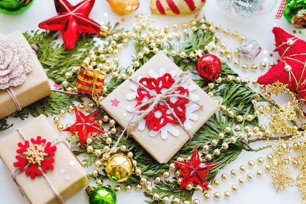 Ramo di thuja di natale, decorazioni e regali avvolti in fiocchi di neve di carta artigianale.