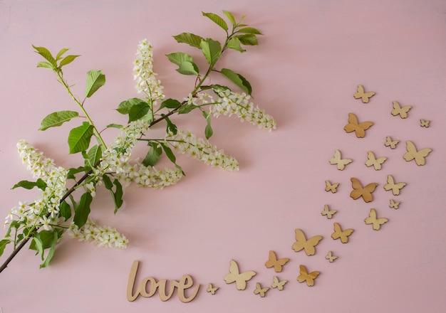 Ramo di uccello bianco ciliegia e farfalle su uno sfondo rosa