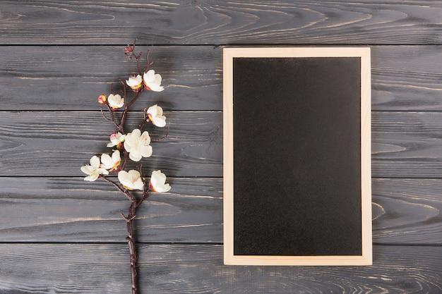 Ramo di un albero con fiori bianchi e lavagna vuota sul tavolo