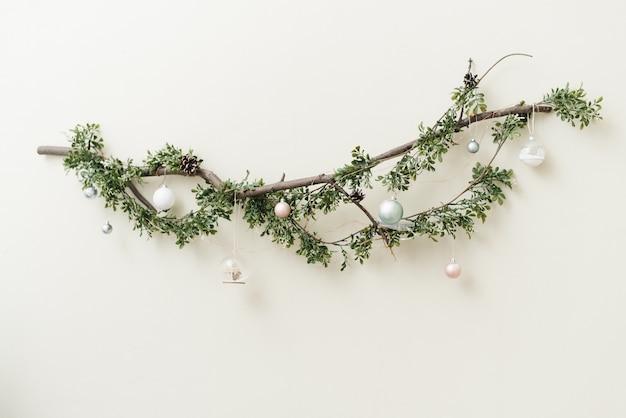 Ramo di un albero sottile con una ghirlanda natalizia verde, palline e giocattoli natalizi in argento e oro.