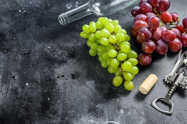 Ramo di uva verde e rossa, una bottiglia, un cavatappi e un tappo di sughero. concetto di vinificazione. sfondo nero.