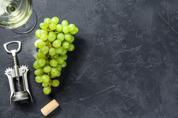 Ramo di uva verde, un bicchiere di vino, un cavatappi e un tappo di sughero. concetto di vinificazione. sfondo nero.