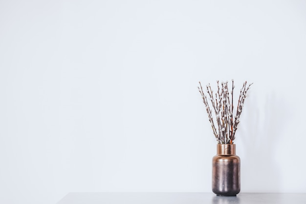 Ramoscelli con gemme in un vaso contro il muro bianco. concetto di inizio primavera, marzo, risveglio della natura o anticipazione della stagione calda