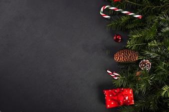 Ramoscelli di abete vicino a bastoncini di zucchero e confezione regalo