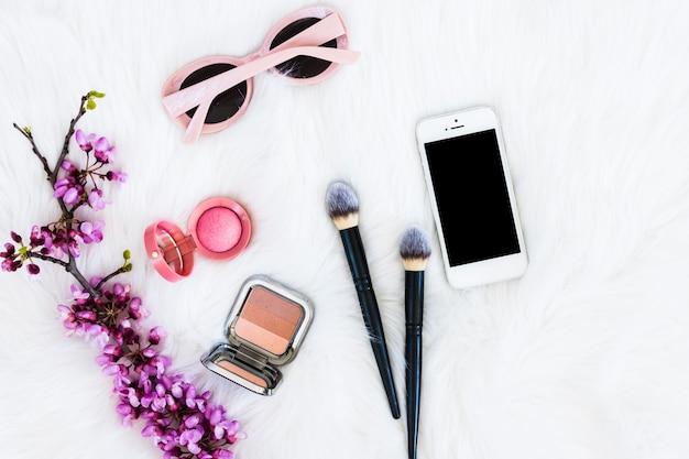 Ramoscello di fiori viola con cipria compatta; pennelli per il trucco; telefono cellulare e occhiali da sole sullo sfondo di pelliccia