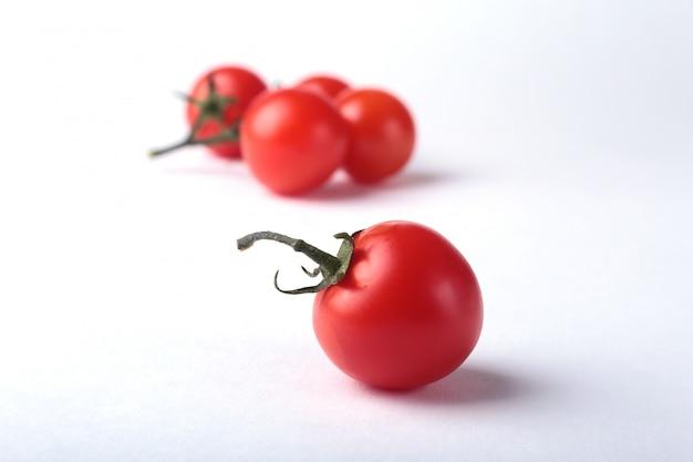 Ramoscello di pomodori freschi con foglie verdi isolato su bianco.
