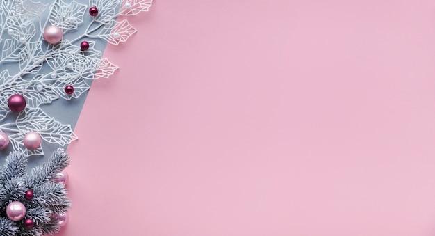 Ramoscello invernale bianco con foglie geometriche lucide e albero di natale artificiale decorato con luci e palline di vetro. piatto natalizio disteso su carta bicolore, rosa e argento. natale con copia-spazio.