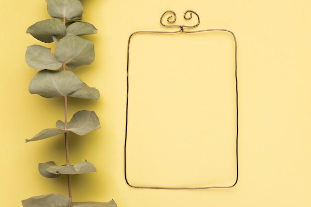 Ramoscello secco vicino alla cornice rettangolare metallica su sfondo giallo