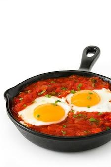 Rancheros messicani di huevos della prima colazione in padella del ferro isolata su fondo bianco