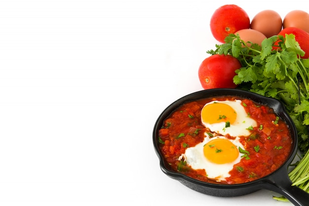 Rancheros messicani di huevos della prima colazione in padella del ferro isolata sullo spazio bianco della copia del fondo