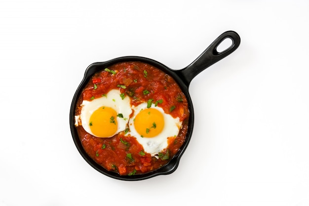 Rancheros messicani di huevos della prima colazione in padella del ferro su bianco