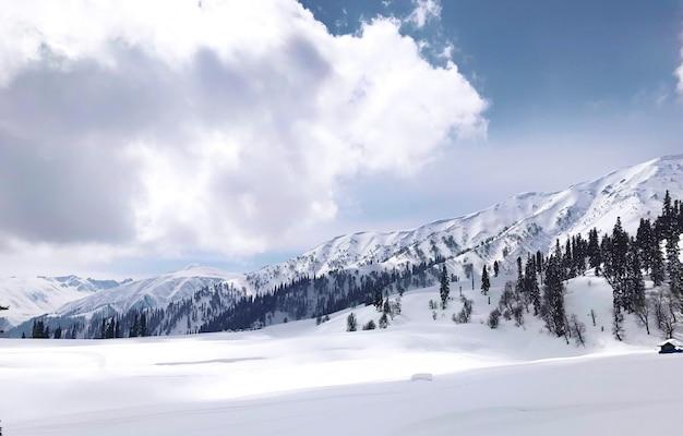 Rango della montagna della neve contro la linea del cielo e la nuvola, scena orizzontale.