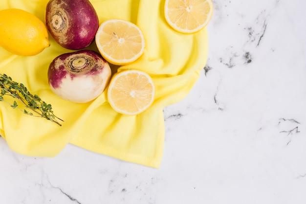 Rape raccolte e limoni tagliati a metà sulla tovaglia gialla contro il contesto di marmo bianco