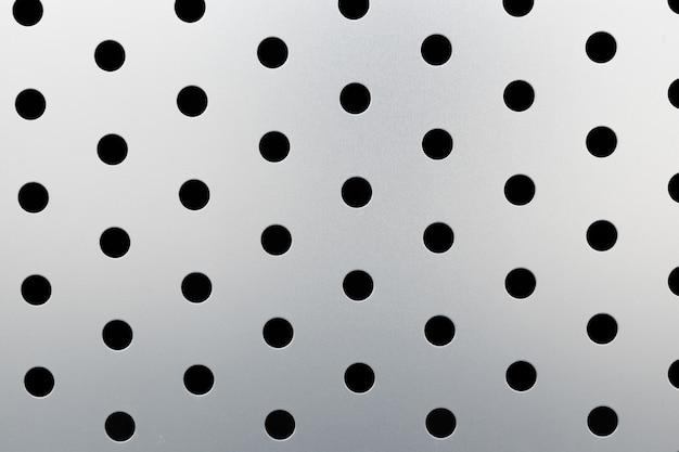 Rapido motivo a punti neri su sfondo grigio, fori tondi sulla superficie del pannello metallico perforato.