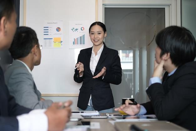 Rapporto del piano finanziario del presente della donna di affari alla squadra del co-lavoratore. il capo della donna discute i dati