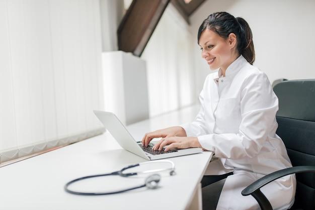 Rapporto di battitura a macchina del medico femminile con il computer portatile.