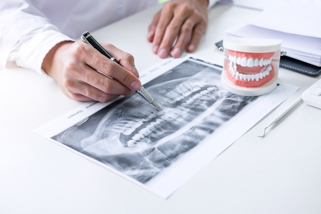 Rapporto di scrittura del medico o del dentista che lavora con la lastra radioscopica del dente