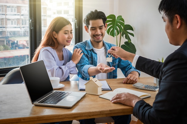 Rappresentante di vendita offre la catena chiave della casa alla giovane coppia asiatica