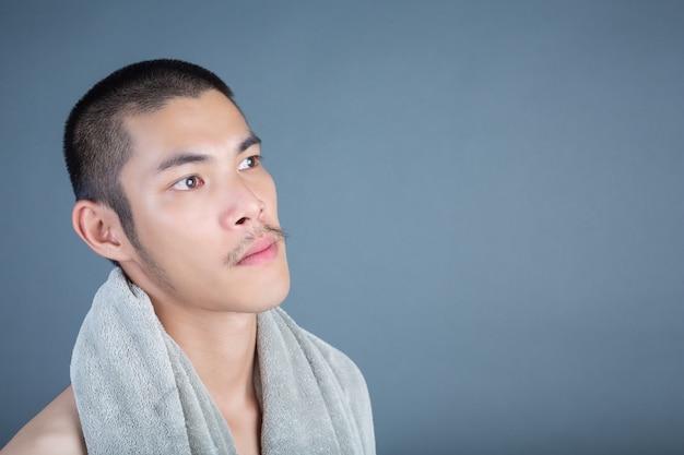 Rasatura bel ragazzo rasato sul viso su grigio