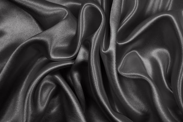 Raso di lusso nero trama di seta per astratto. tono scuro del tessuto