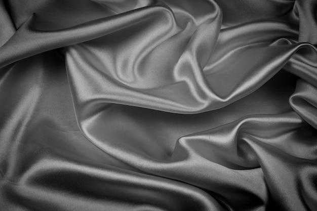 Raso lussuoso di seta nera per sfondo astratto. tono scuro del tessuto