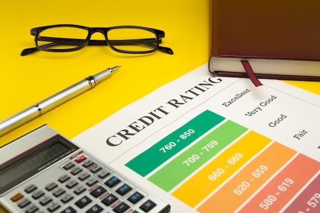 Rating di credito su un tavolo giallo, penna, occhiali, notebook e calcolatrice