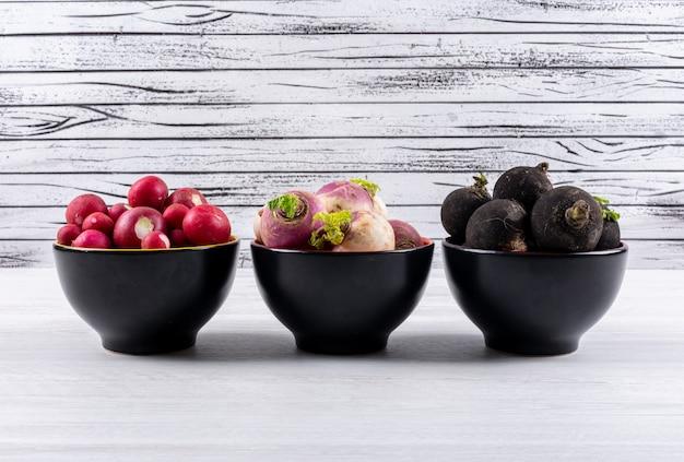 Ravanelli freschi differenti di colore in tre ciotole nere su una tavola di legno bianca.
