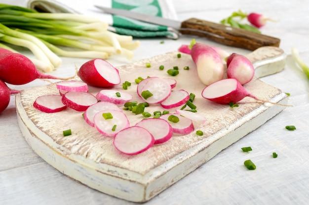 Ravanelli rossi freschi affettati e giovani cipolle verdi su fondo di legno bianco. dieta sana con ravanello. ingredienti per un'insalata di verdure primaverile leggera. avvicinamento