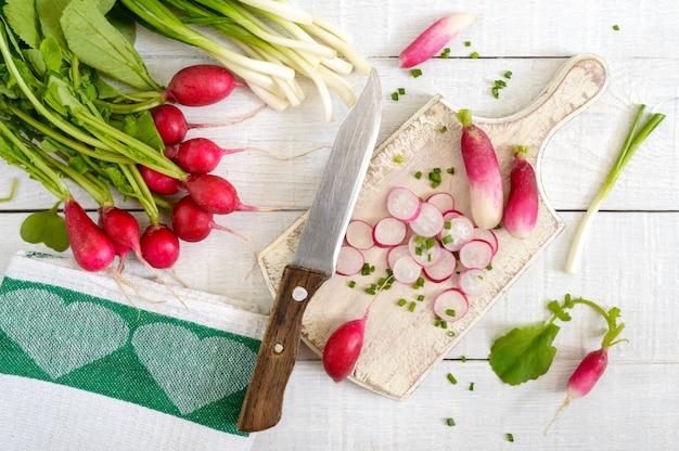 Ravanelli rossi freschi affettati e giovani cipolle verdi su fondo di legno bianco.