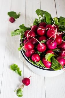 Ravanelli rossi in ciotola sul tavolo di legno