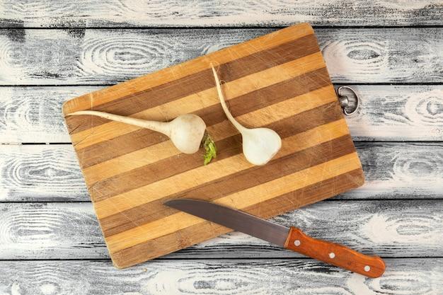 Ravanello bianco maturo sullo scrittorio di legno marrone e sul pavimento rustico