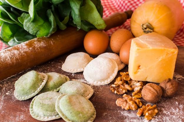 Ravioli crudi bianchi e verdi con ingredienti in tavola di legno