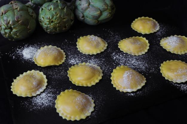 Ravioli crudi fatti in casa di carciofi pronti da cuocere su un piatto di ardesia. pasta italiana