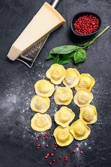 Ravioli freschi non cotti. cucina italiana casalinga. sfondo nero. vista dall'alto.