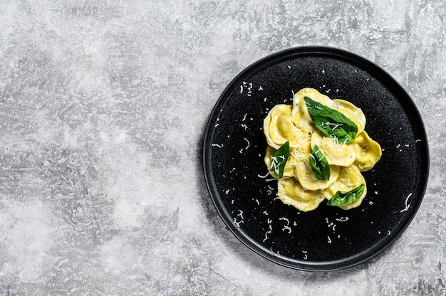 Ravioli italiani con formaggio e basilico. sfondo grigio. vista dall'alto