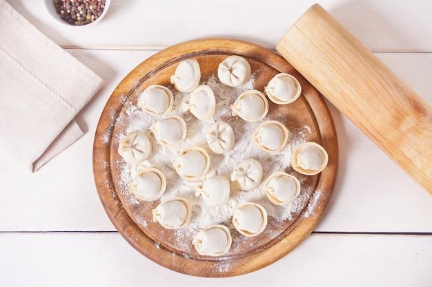 Ravioli italiani crudi casalinghi degli gnocchi della carne di pelmeni sul tagliere.