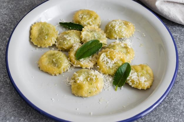 Ravioli italiani cucinati freschi con la ricotta e gli spinaci sulla tavola grigia
