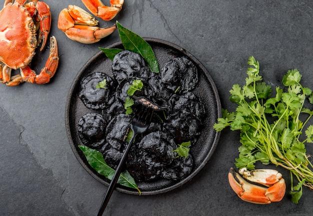 Ravioli neri italiani con gamberi di mare e granchi su lastra nera, ardesia di pietra grigia. vista dall'alto