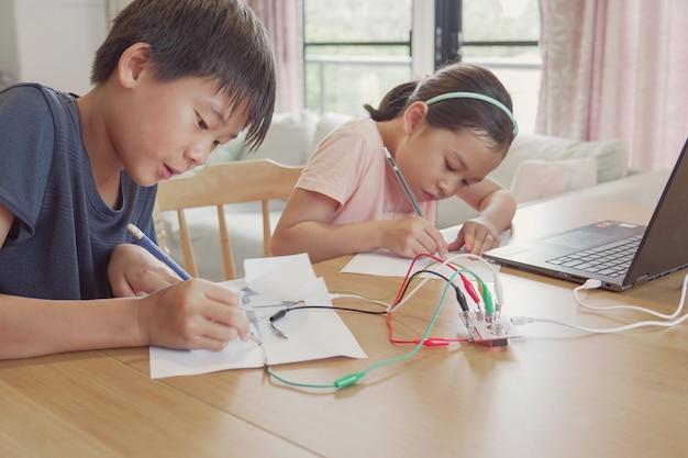 Razza mista giovani bambini asiatici che imparano a programmare insieme, imparano da remoto a casa, scienza stem, educazione homeschooling, distanza sociale, concetto di isolamento