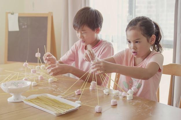 Razza mista giovani bambini asiatici costruendo la torre con spaghetti e marshmallow imparando da remoto a casa, scienza stem, educazione homeschooling, distanza sociale, concetto di isolamento