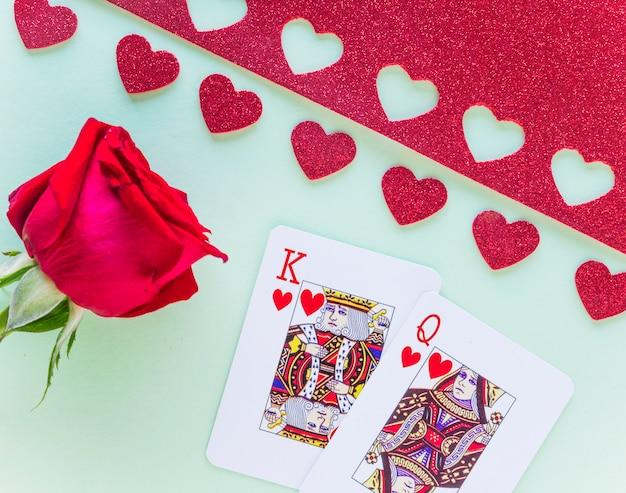 Re e regina di cuori che giocano a carte con rosa