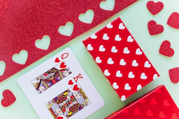 Re e regina di cuori che giocano a carte con scatola regalo