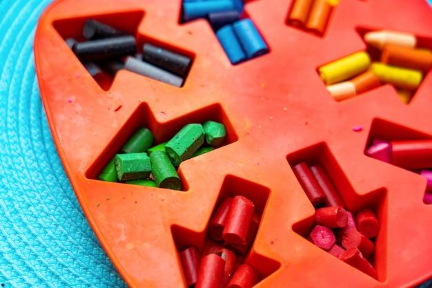 Realizzare matite di cera fatte in casa dai rottami di vecchi pastelli sciogliendoli nel forno ad alta temperatura in una forma di silicone. hack di vita