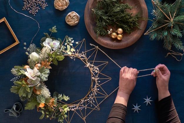 Realizzazione di ghirlanda natalizia decorativa su classico lino blu