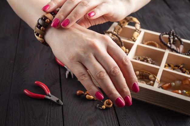 Realizzazione di gioielli fatti a mano. donna che prova un braccialetto fatto in casa