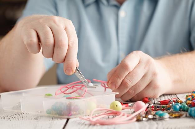 Realizzazione di gioielli fatti a mano, vista frontale di mani maschili